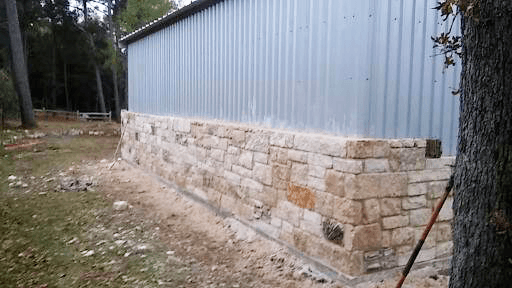 Stone siding on a long side of the metal shop.  Note how it fits on the cement slab.