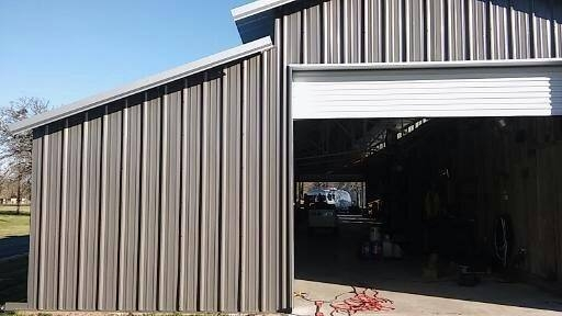 View of one end showing the new gray metal siding and the white roll-up door.  metal barn refurbishment