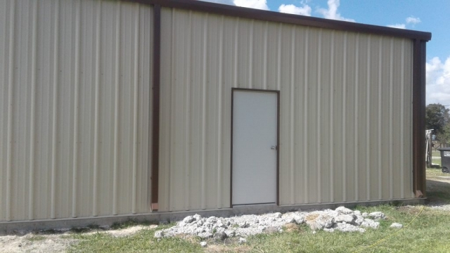 Walk-through door and gutter downspouts on steel building. metal barndominium