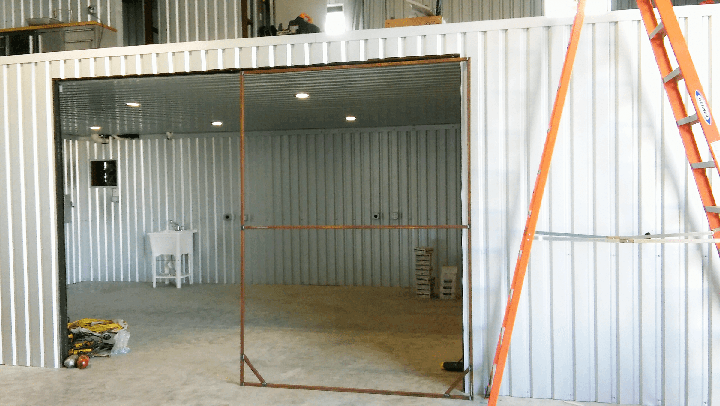 Working on the custom fabricated doors for the area under the mezzanine.