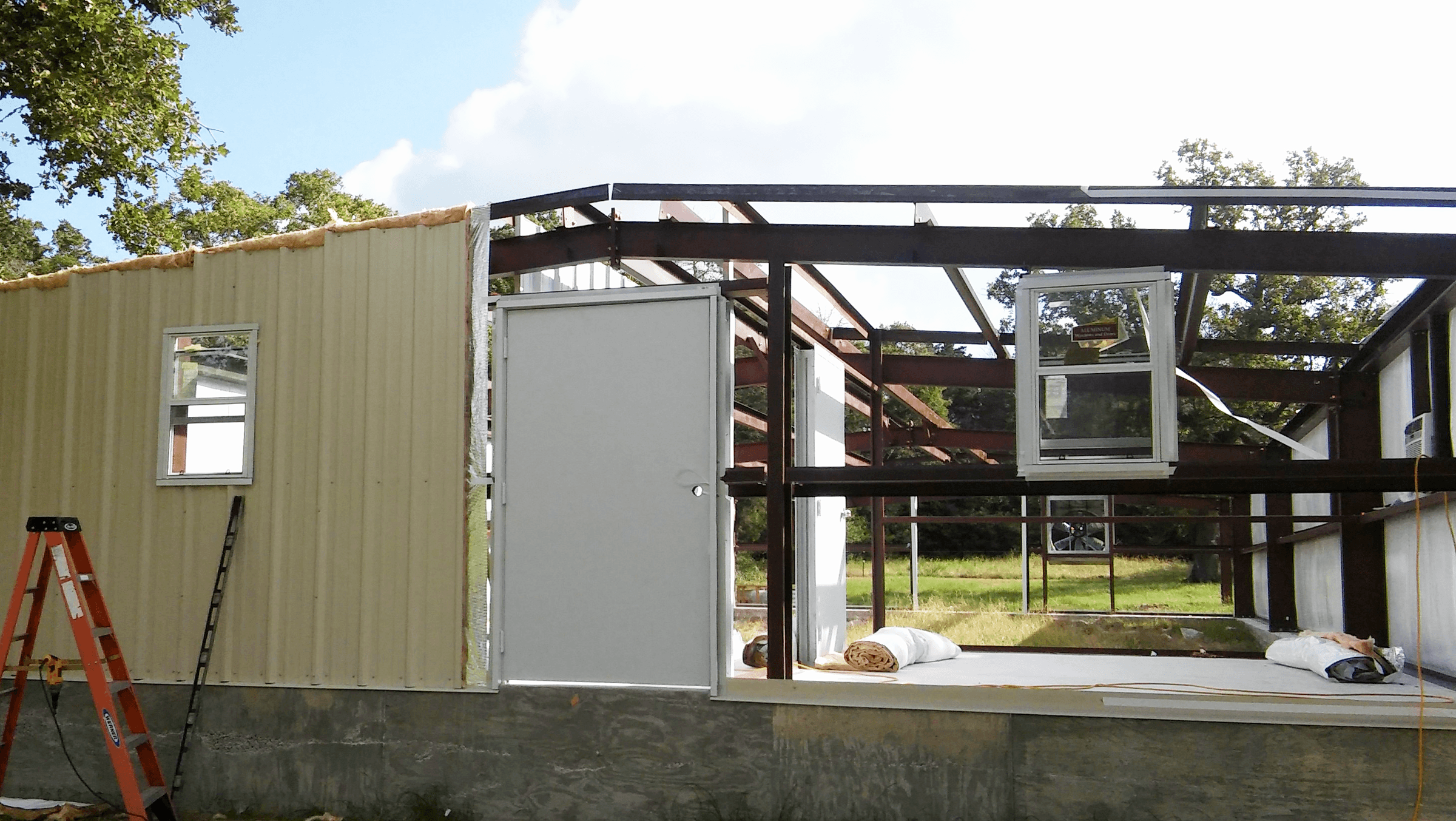 Some of the insulation and metal walls are up.