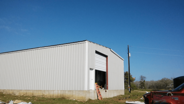 Metal building showing missing roofline trim and lack of door trim.