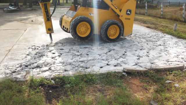 Breaking up the old concrete pad to make way for the new, larger pad.