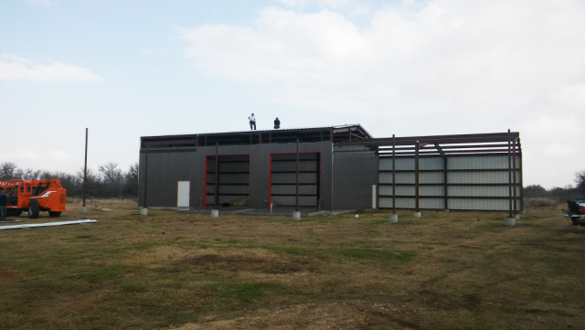 """Metal 2-story barndominium with attached mechanic shop and wash bay.  20' x 60' overhang with 8"""" concrete base."""