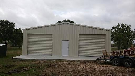 Metal garage with roll doors and center walk-through door.