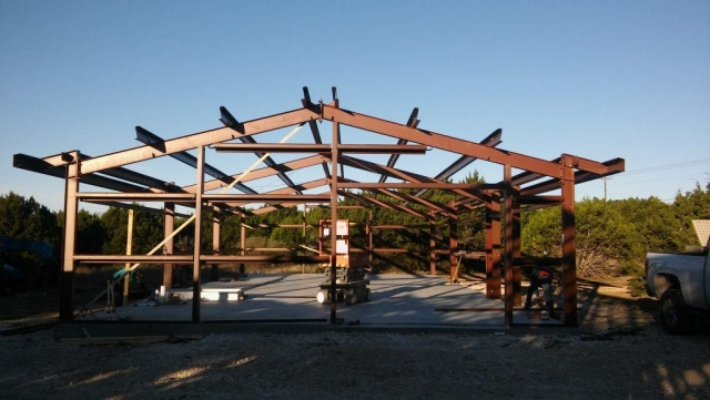 Red iron framework for custom steel building designed and erected by Simply Metal Structures, LLC.