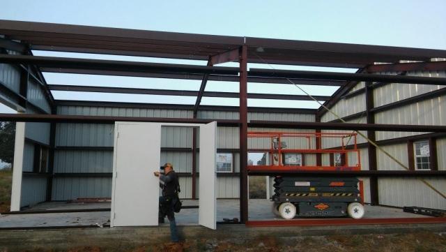 Installing the double swing doors on the custom metal shop building.